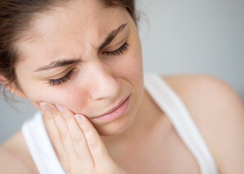 Woman holding her face in pain because of a cracked tooth. This can be repaired by Dr. Simon Choyee in Whittier, CA