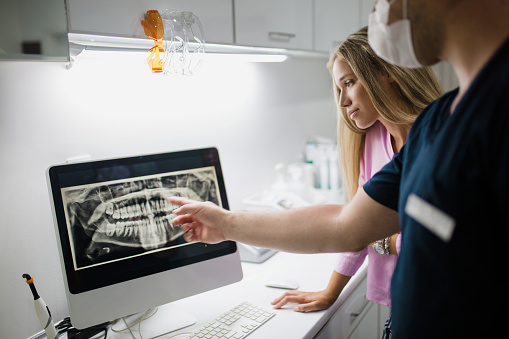 A dental Assistant viewing a digital x-ray while a patient is being scanned on 3D cone beam scanner  at Simon K. Choyee, DDS, Inc.